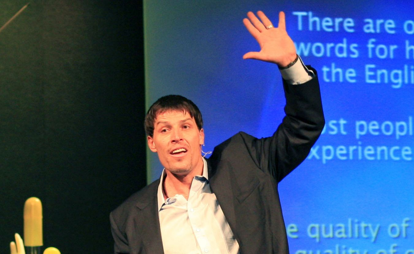 Tony Robbins at a Ultimate Power event holding his hand in the air.