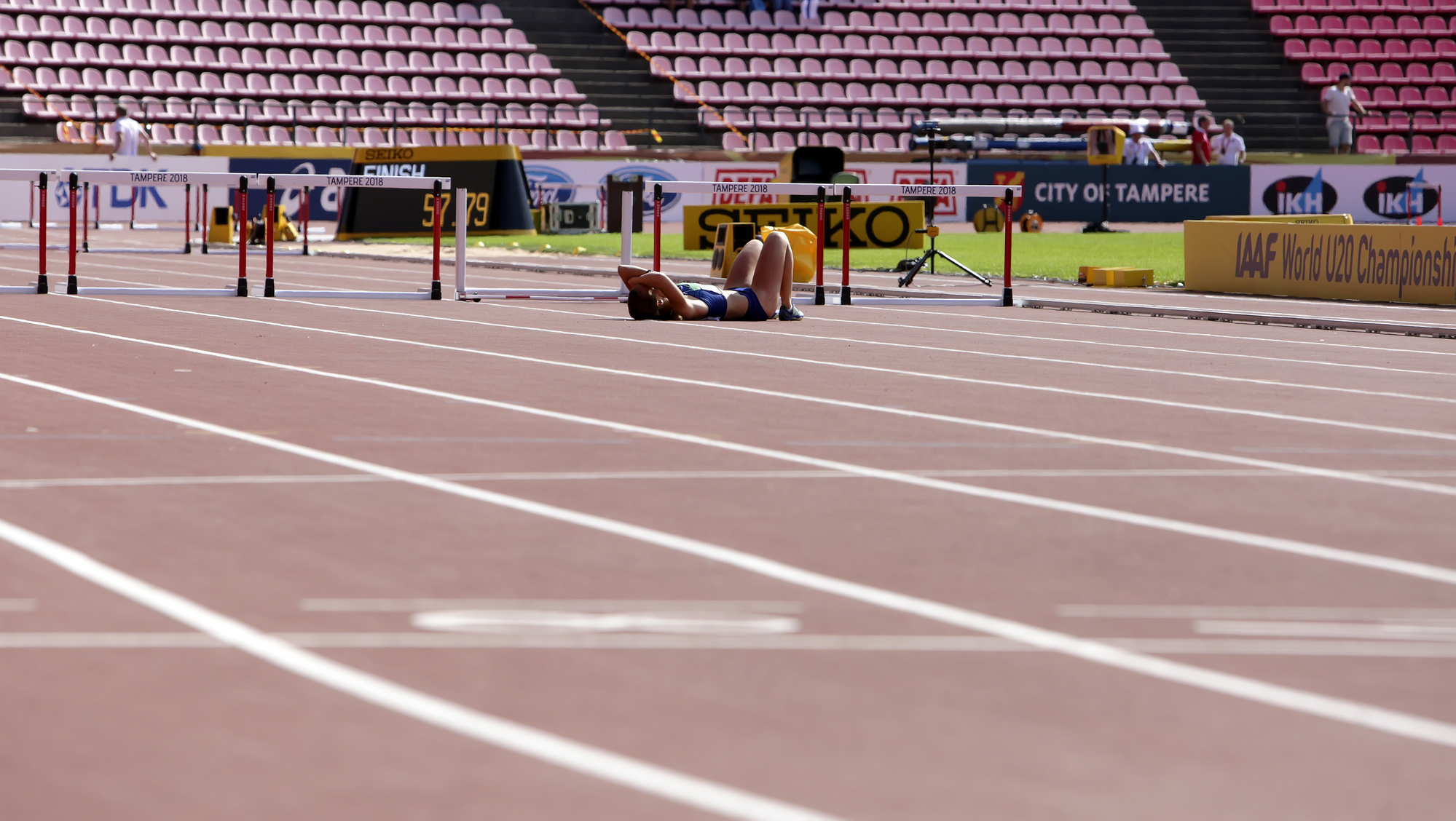 steeple chase athlete laying on track after losing because not good enough